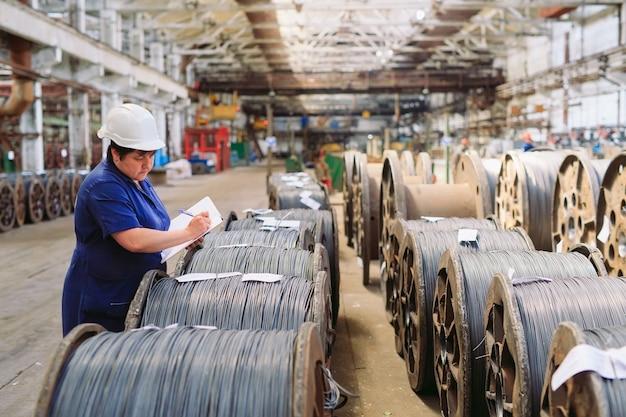Draht, armaturen in lagern. arbeiter neben einem bündel mit catalkoy. industrielager im metallurgischen werk.