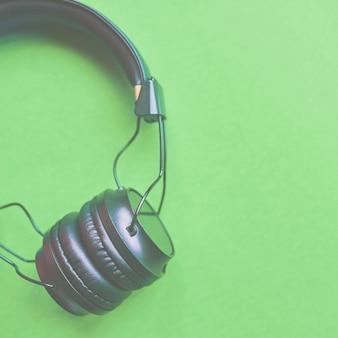 Drahtlose kopfhörer auf buntem grünem hintergrund für den musikton lokalisiert. 1x1 ernte