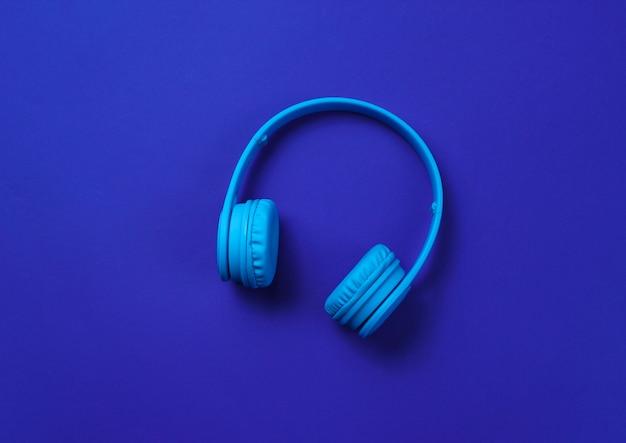 Drahtlose kopfhörer auf dunkelblauem hintergrund. draufsicht.