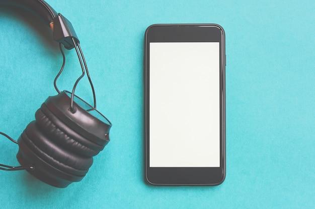 Drahtlose kopfhörer und modell smartphone auf buntem hintergrund