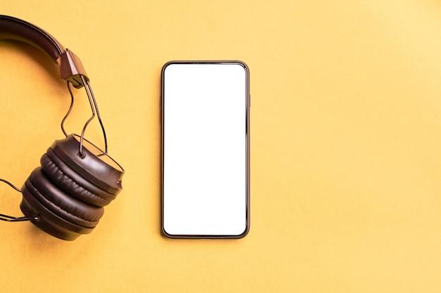 Drahtlose schwarze kopfhörer und rahmenloser smartphone auf buntem gelbem hintergrund