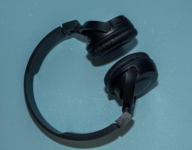 Drahtlose schwarze kopfhörerseitenansicht lokalisiert auf blauer oberfläche.