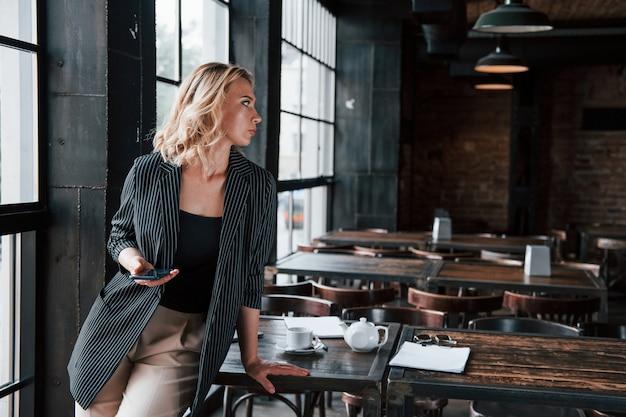 Drahtlose technologien. geschäftsfrau mit lockigem blondem haar drinnen im café tagsüber.