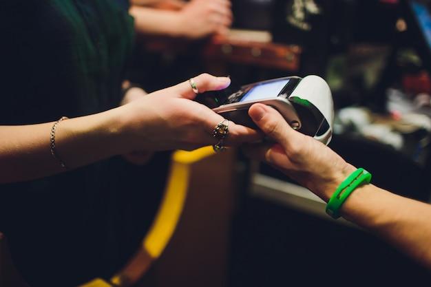 Drahtlose zahlung für den kauf eines smartphones im geschäft über das zahlungsterminal.