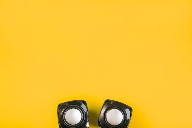 Drahtloser bluetooth-lautsprecher auf gelbem hintergrund