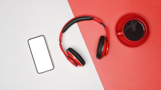 Drahtloser kopfhörer der draufsicht, smartphone und kaffeetasse auf weißem und rotem hintergrund.