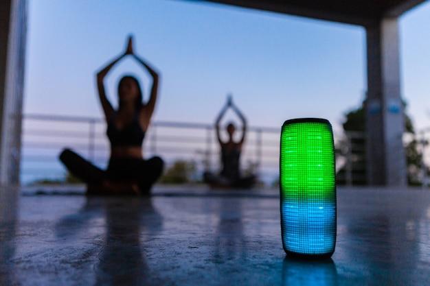 Drahtloser lautsprecher mit farbenfroher hintergrundbeleuchtung im vordergrund der gesellschaft von freunden, die yoga in der abenddämmerung musik hören