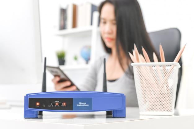 Drahtloser router und frau, die einen smartphone im büro verwendet