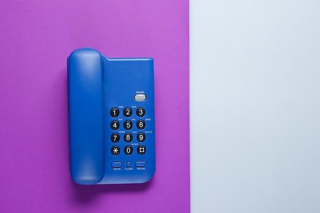 Drahtloses bürotelefon auf lila grauem tisch