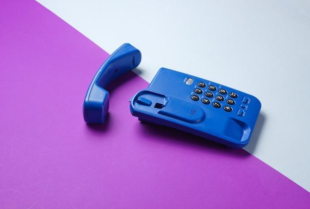Drahtloses bürotelefon mit mobilteil auf lila grauem tisch.