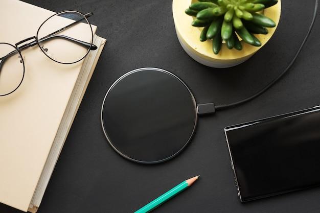 Drahtloses laden auf einer schwarzen tafel mit einem buch, einem bleistift, einem smartphone, einer brille und einer pflanze.