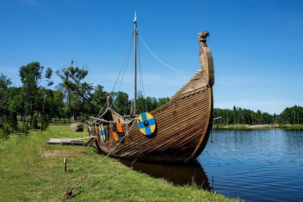 Drakkar, ein wikingerboot, das in der nähe des grasbewachsenen ufers festgemacht hat. runde schilde am gehäuse.