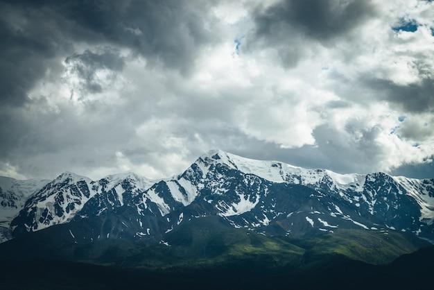 Dramatische berglandschaft mit großem schneebedeckten bergrücken unter bewölktem himmel. dunkle atmosphärische hochlandlandschaft mit hochgebirge bei bedecktem wetter. ehrfürchtige große berge unter grauen wolken.