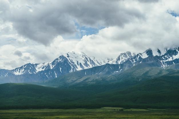 Dramatische berglandschaft mit schneebedeckter bergkette unter niedrigen wolken. atmosphärische hochlandlandschaft mit hohem bergrücken über grünem wald bei bedecktem wetter. toller blick auf die bergwand.