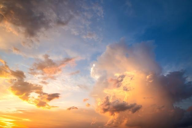 Dramatische bewölkte sonnenuntergangslandschaft mit geschwollenen wolken beleuchtet durch orange untergehende sonne und blauen himmel.