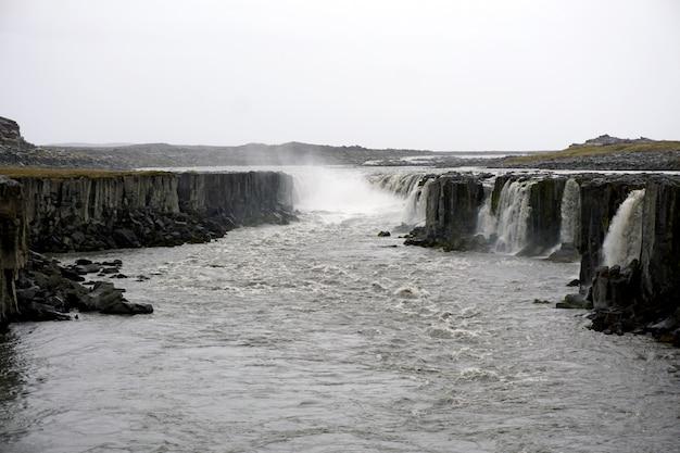Dramatische landschaft in island mit grauem himmel. selfoss wasserfall im nationalpark jokulsargljufur.
