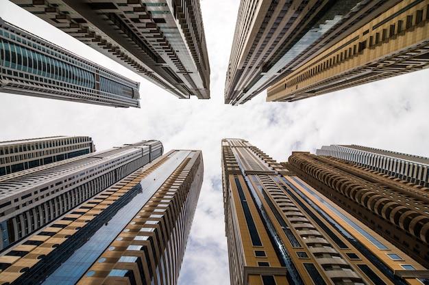 Dramatische perspektive mit niedriger winkelansicht von wolkenkratzern, die zum himmel, dubai aufblicken. fluchtpunkt