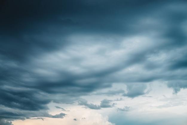 Dramatische wolkengebilde. sonniges licht durch dunkle schwere gewitterwolken vor dem regen.