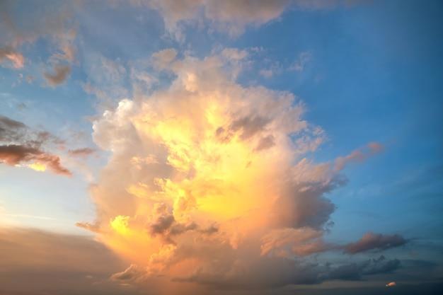 Dramatische wolkenlandschaft mit geschwollenen wolken, die durch orange untergehende sonne und blauen himmel beleuchtet werden.