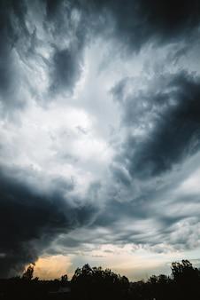Dramatische wolkenlandschaft. sonniges licht durch dunkle schwere gewitterwolken vor regen. bedecktes regnerisches schlechtes wetter. sturmwarnung. sonnenlicht im stürmischen bewölkten himmel.