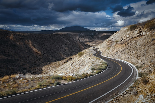 Dramatische wolkenlandschaft über leere straße durch landschaftlich reizvolle schlucht bei santa rosalia, baja california, mexiko