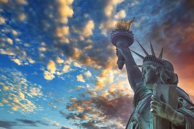 Dramatischer blick auf die freiheitsstatue mit manhattan in einem roten sonnenuntergangshintergrund in amerika