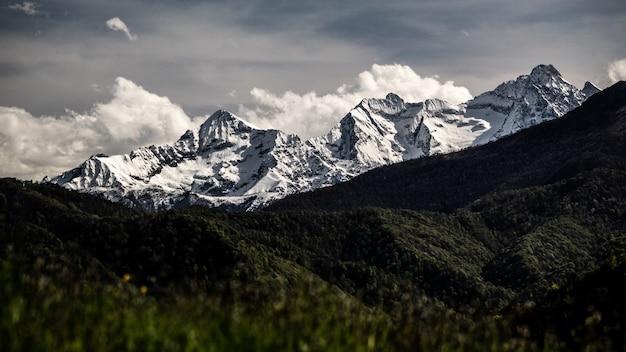 Dramatischer blick auf die italienischen alpen hinter einem tal von bäumen