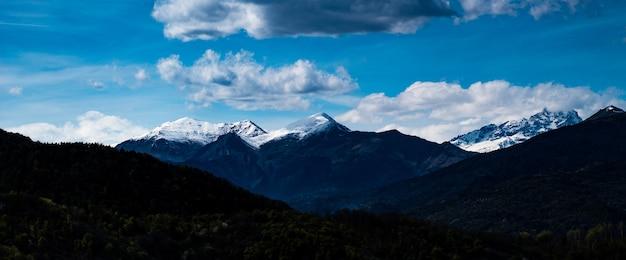 Dramatischer blick auf die italienischen alpen und wolken hinter einem tal von bäumen
