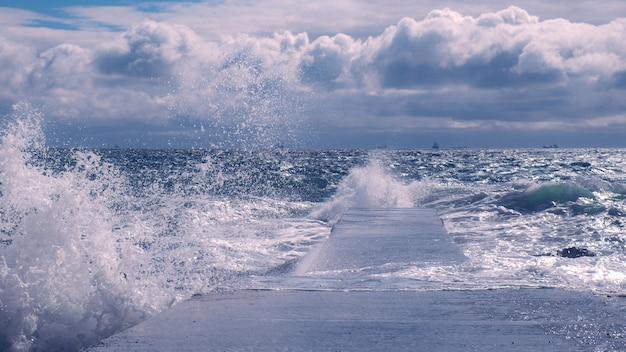 Dramatischer blick auf meereswellen, die gegen den betonpier krachen