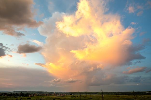 Dramatischer gelber sonnenuntergang über ländlichem gebiet mit stürmischen geschwollenen wolken beleuchtet durch orange untergehende sonne und blauen himmel.