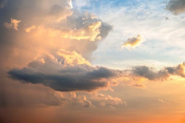 Dramatischer himmel bei sonnenuntergang mit geschwollenen wolken beleuchtet durch orange untergehende sonne.