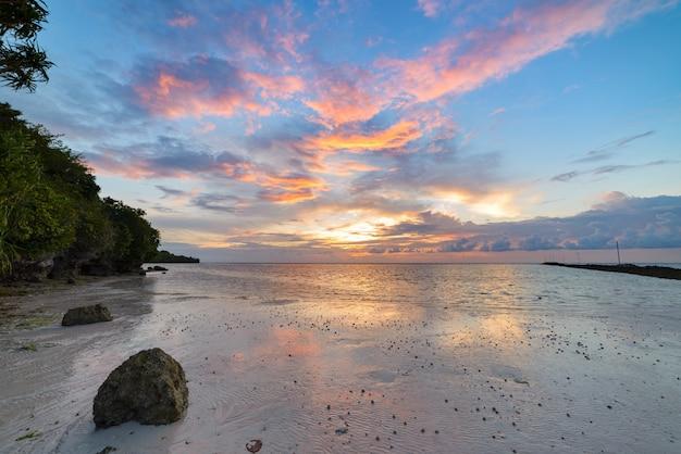 Dramatischer himmel des sonnenuntergangs auf tropischem wüstenstrand, korallenriffreflexion keine leute, reiseziel, indonesien wakatobi