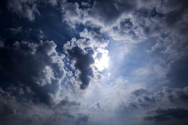 Dramatischer himmel mit grauen stürmischen wolken im sonnenlichthimmel.