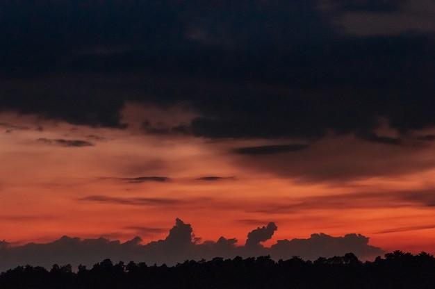 Dramatischer roter himmel des schönen sonnenuntergangs mit dunklen wolken