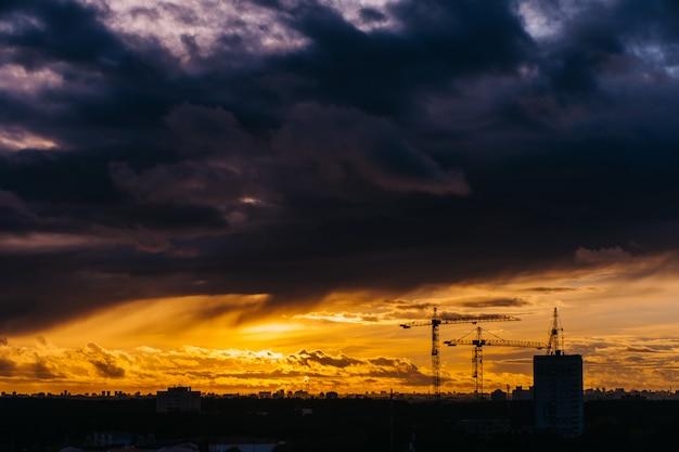 Dramatischer sonnenuntergang über der stadt bedeckt durch wolken über minsk, weißrussland. turmdrehkran-silhouette.