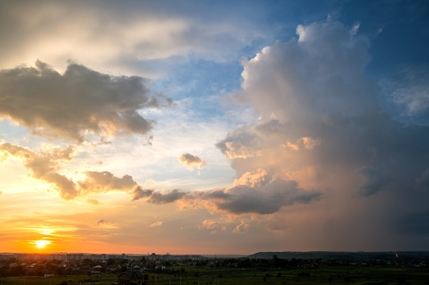 Dramatischer sonnenuntergang über ländlichem gebiet mit stürmischen geschwollenen wolken beleuchtet durch orange untergehende sonne und blauen himmel.