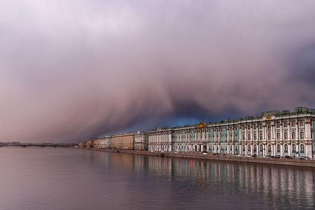 Dramatischer sonnenuntergang und wetterfront mit schneesturmgefahr im frühjahr über der eremitage in st. petersburg. blick auf die newa.