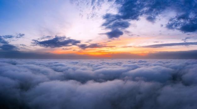 Dramatischer sonnenuntergangshimmel über den flauschigen wolken aus der luftansicht. schöne wolkenlandschaft.