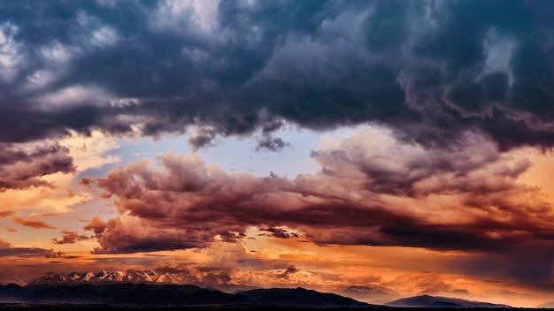 Dramatisches licht durch die wolken vor dem hintergrund eines aufregenden, vibrierenden stürmischen himmels bei sonnenuntergang, morgengrauen in den bergen.