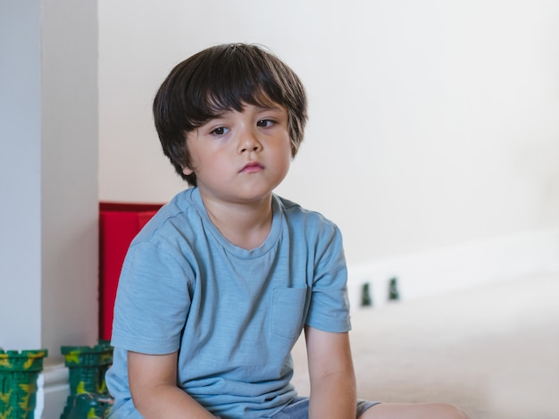 Dramatisches porträt müdes kind, das allein sitzt und tief in gedanken hinausschaut