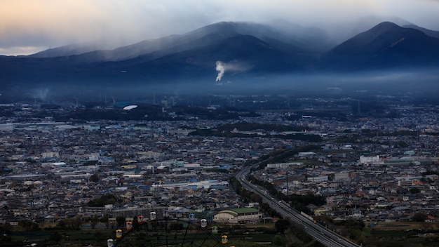 Dramatisches und dunkles prozessstadtbild im strom- und smogschichtgebirgshintergrund in japan