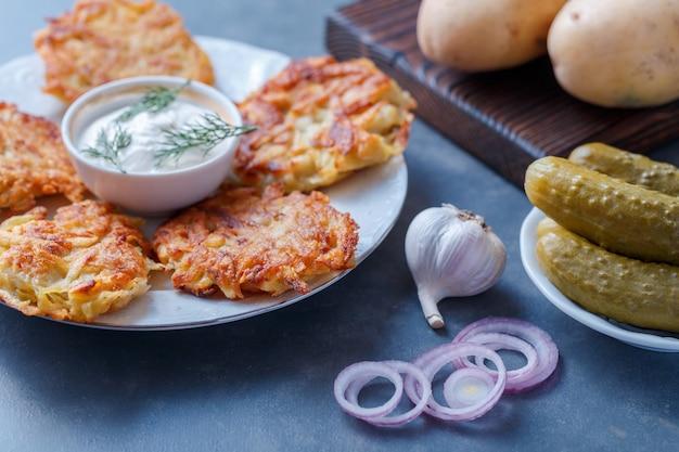 Draniki, kartoffelpuffer. kartoffelpuffer liegen auf einem teller.