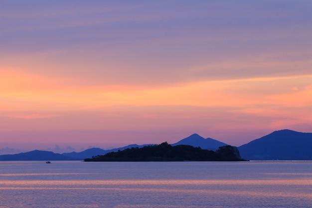 Drastischer pastellsonnenunterganghimmel und tropisches meer mit inselvordergrund