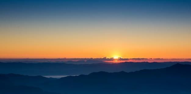 Drastischer sonnenuntergang- und sonnenaufganghimmel des landschaftspanoramas auf gebirgsschicht