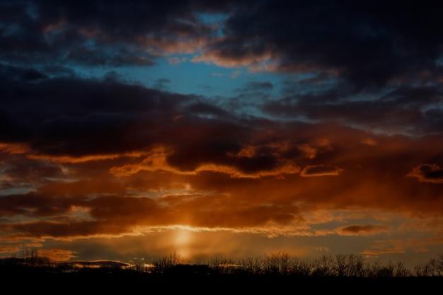Drastischer sonnenuntergang und sonnenaufganghimmel. schöner brennender orange und purpurroter sonnenuntergang