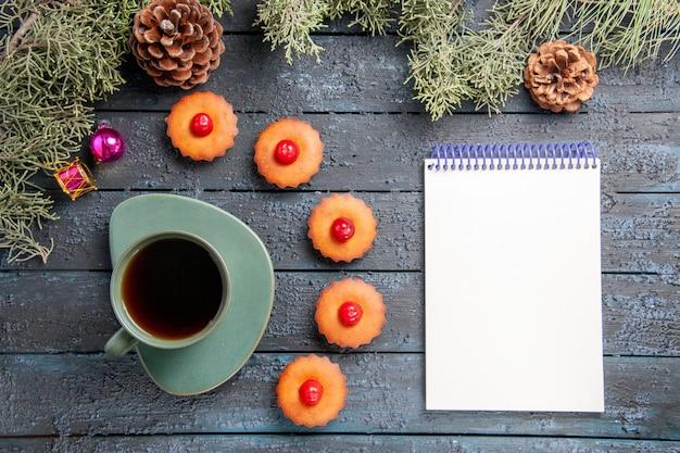 Draufsicht abgerundete kirschcupcakes tannenbaumzweige weihnachtsspielzeug tannenzapfen eine tasse tee ein notizbuch auf dunklem holztisch