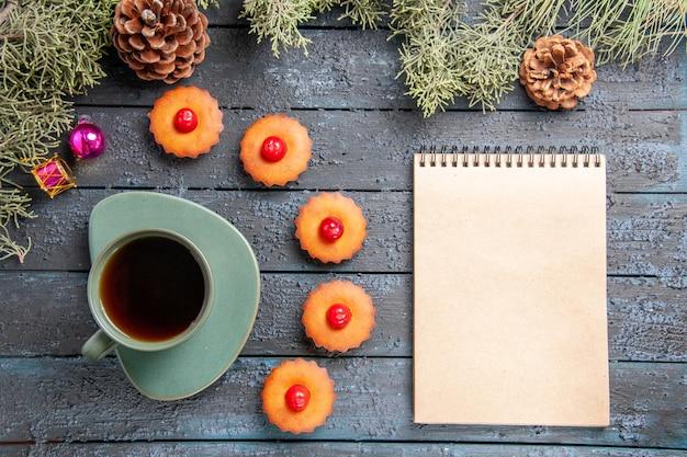 Draufsicht abgerundete kirschcupcakes tannenbaumzweige weihnachtsspielzeugkegel eine tasse tee ein notizbuch auf dunklem holztisch
