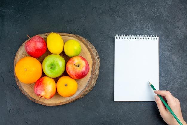Draufsicht äpfel zitronenorangen auf holzbrett notizbuchstift in weiblicher hand auf dunkler oberfläche