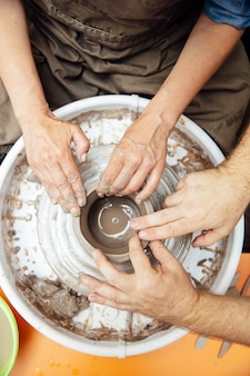 Draufsicht an spinnendem lehm der älteren frau auf einem rad mit lehrer an der tonwarenklasse