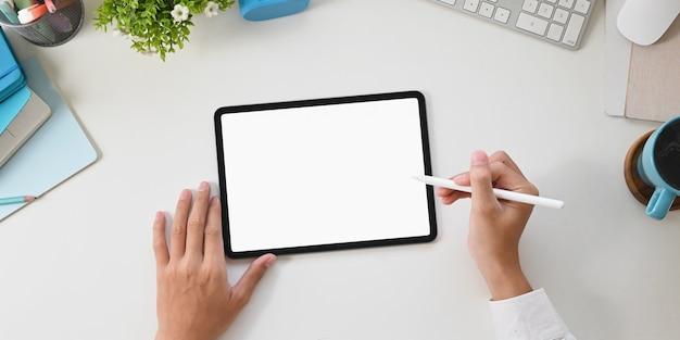 Draufsicht arbeiten schreibtischhände zeichnen auf einem weißen leeren bildschirmcomputertablett.